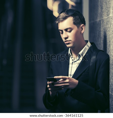 Young handsome man with smart phone standing at the wall - stock photo