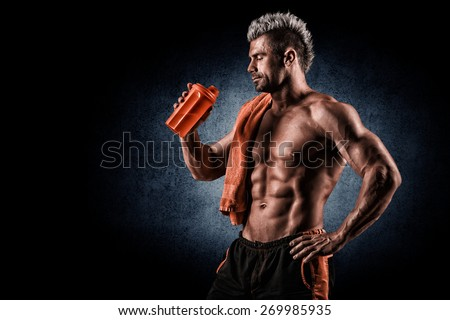 young handsome man with strong muscles, protein drink after training - stock photo