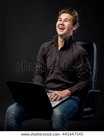Young handsome man working with laptop on a black background - stock photo