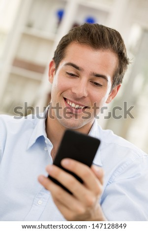 Young handsome man writting SMS on mobile phone. - stock photo