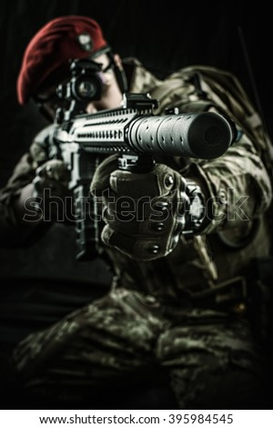 Young handsome military man in italian camouflage aiming from automatic rifle, he wearing red beret and gloves. Focus on the gun muzzle