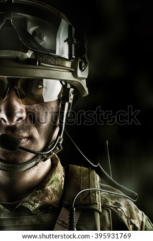 Young handsome military man in italian camouflage wearing helmet, glasses and radio set