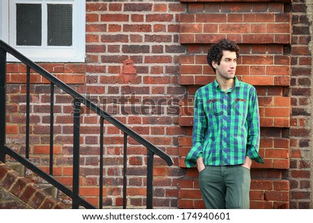 young handsome model posing against brick wall - stock photo