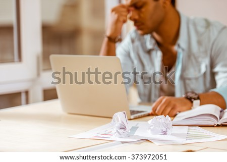Young handsome mulatto businessman in casual clothes using laptop and having headache while working in office - stock photo