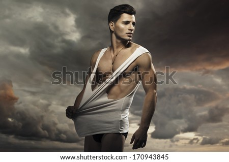 Young handsome muscular guy in a nature  - stock photo