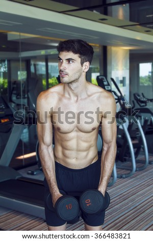 Young handsome muscular man exercising in the gym. Dumbbell bicep curl exercise in standing position next to the weight rack. Exercise with the smile.  - stock photo
