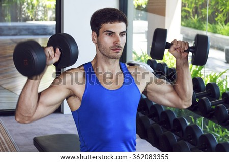 Young handsome muscular man exercising in the gym. Dumbbell shoulder press exercise in sitting position next to the weight rack. - stock photo