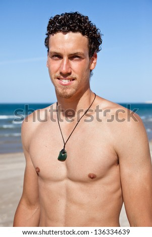 Young handsome muscular man on the beach. Surfer type.