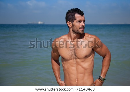 Young handsome muscular man standing in blue water looking away. - stock photo