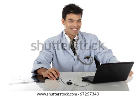 Young handsome Nepalese male doctor with stethoscope sitting at desk working with the laptop. Studio shot. White background. - stock photo