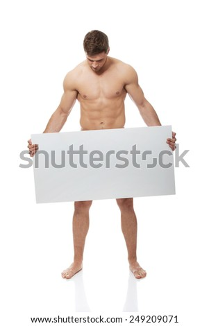 Young handsome nude man covering his self with empty banner. - stock photo