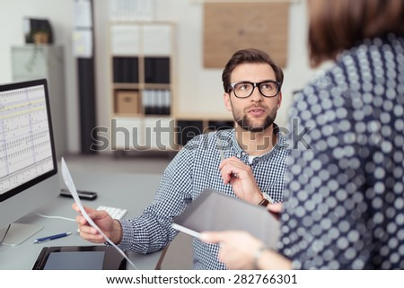 Young Handsome Office Man Talking to his Female Manager While Holding a Paper at his Working Table with Computer. - stock photo
