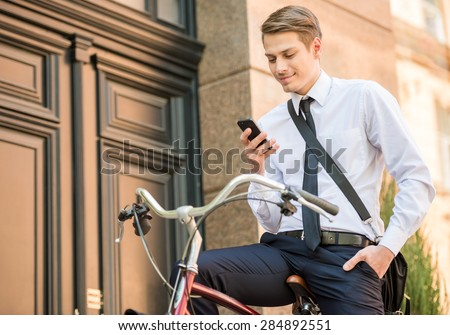 Young handsome office worker going to work on his bicycle. Healthy lifestyle concept. - stock photo