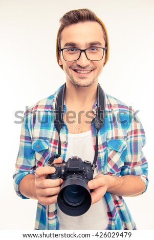 Young handsome photographer taking a photo - stock photo