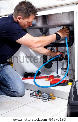 Young handsome plumber doing reparation at the kitchen. - stock photo