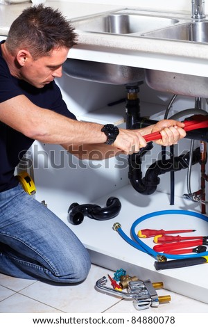 Young handsome plumber doing reparation at the kitchen.