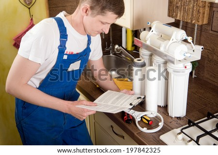 Young handsome plumber plumbing repairs. Replacement water filter - stock photo