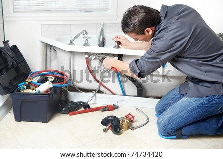 Young handsome plumber repearing bath tub. Service. - stock photo