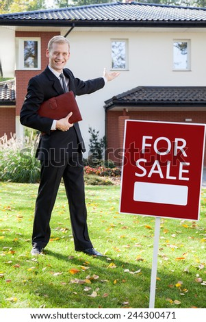 Young handsome real estate agent showing the house for sale