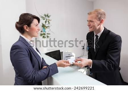 Young handsome receptionist giving woman the key to her room - stock photo
