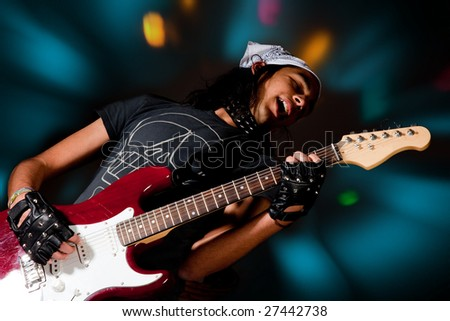 Young handsome rock singer against a dark background with spot lights - stock photo