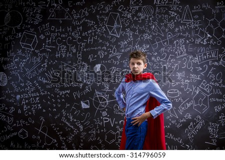 Young handsome school boy with red cape in front of big blackboard - stock photo