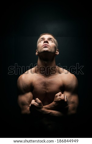 young handsome sexy man looking up on a dark background - stock photo