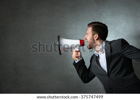 Young handsome shouting man using megaphone over grey background