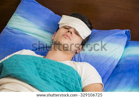 Young handsome sick or unwell man in bed with a flu or fever  - stock photo