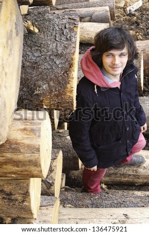 Young Handsome Smiling Man Standing near Wooden Logs - stock photo