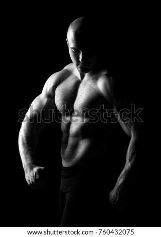 Young, handsome sports guy with a naked torso isolated on dark background