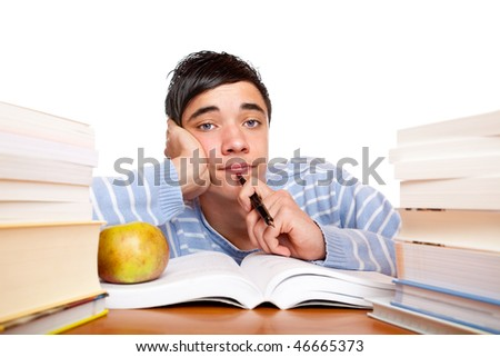 Young handsome student sitting on a desk between study books and looks frustrated. Isolated on white. - stock photo
