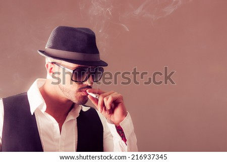 Young handsome stylish male model wearing a hat smoking a cigarette - stock photo
