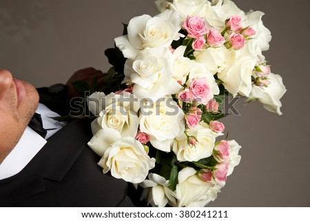 Young handsome stylish man with great smile in elegant black suit holding bouquet of flowers.  - stock photo