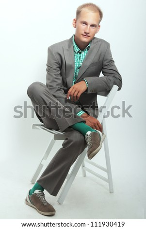 Young handsome successful business man smiling full size shot sitting on a chair in studio isolated - stock photo