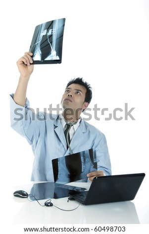 Young handsome successful Nepalese male doctor at desk studying x-ray photo. Studio shot. white background. - stock photo