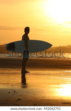 Young handsome surfer man standing with surfboard