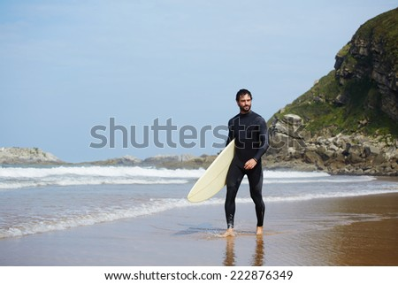 Young handsome surfer man walking with surfboard on the beach, handsome surfer walks carrying surfboard with big mountain rock on background, perfect sunny day for surfing on big waves - stock photo