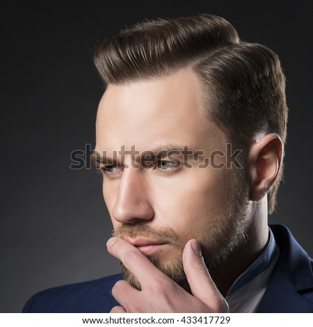 Young handsome thoughtful bearded caucasian man with blue eyes and a hand near chin. Perfect skin and hairstyle. Wearing blue suit. Studio portrait on gradient black to grey background. Toned