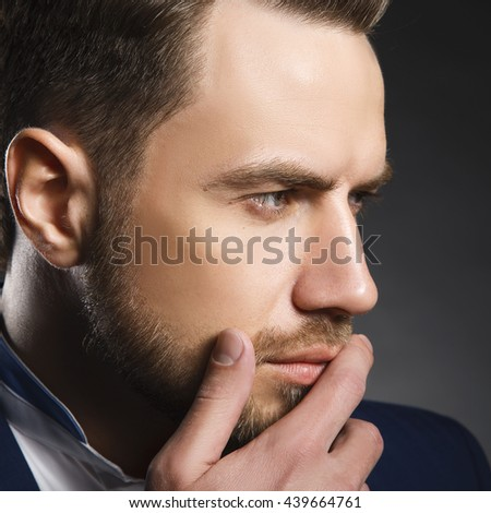 Young handsome thoughtful bearded caucasian man with blue eyes and a hand near chin. Perfect skin and hairstyle. Wearing blue suit.Studio portrait on gradient black background. Toned