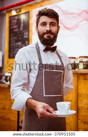 Young handsome waiter with beard holding a cup while standing in a cafe - stock photo