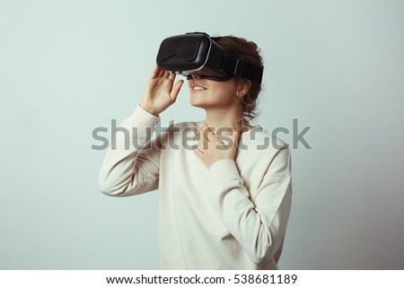 Young handsome woman wearing virtual headset. Excited Hipster using VR glasses. Empty studio wall background