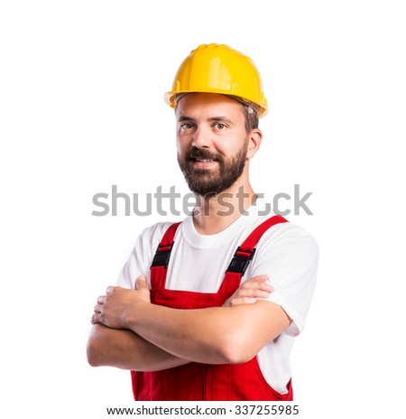 Young handsome worker in red overalls. Studio shot on white background