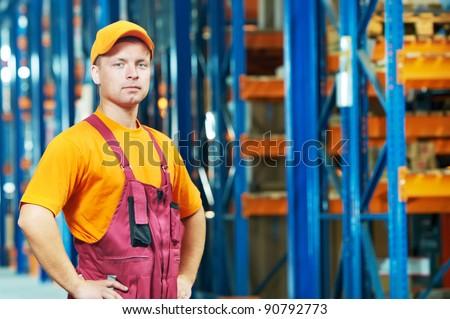 young handsome worker man in uniform in front of warehouse rack arrangement stillages - stock photo