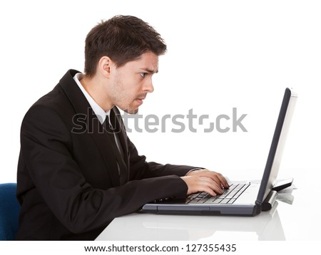 Young handsome young businessman seated at his desk behind his laptop computer looking at the camera