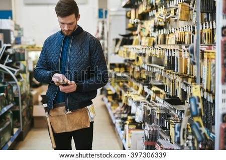 Young handyman checking information on his mobile before making a purchase in a hardware store - stock photo