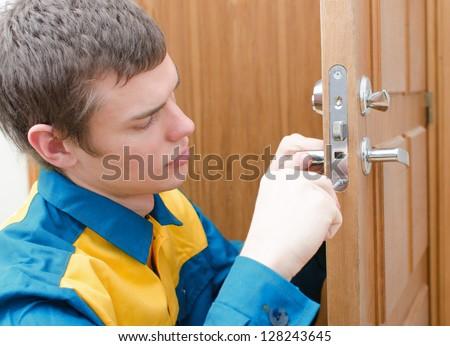 Young handyman in uniform changing door lock - stock photo