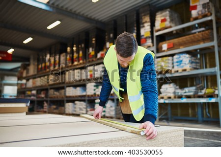 Young handyman working in a building supplies or hardware warehouse checking lumber on a table - stock photo