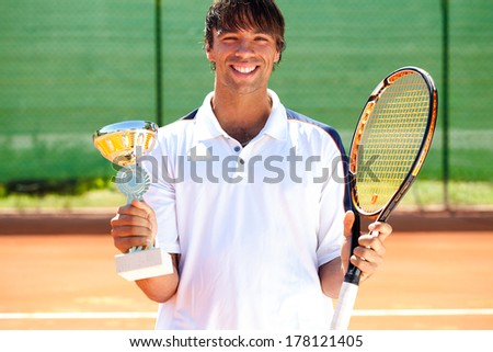 Young happiness tennis player won the cup, trophy