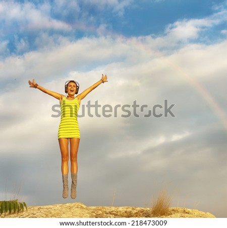 Young happiness woman in headphones is jumping against blue sky with rainbow on sky  - stock photo
